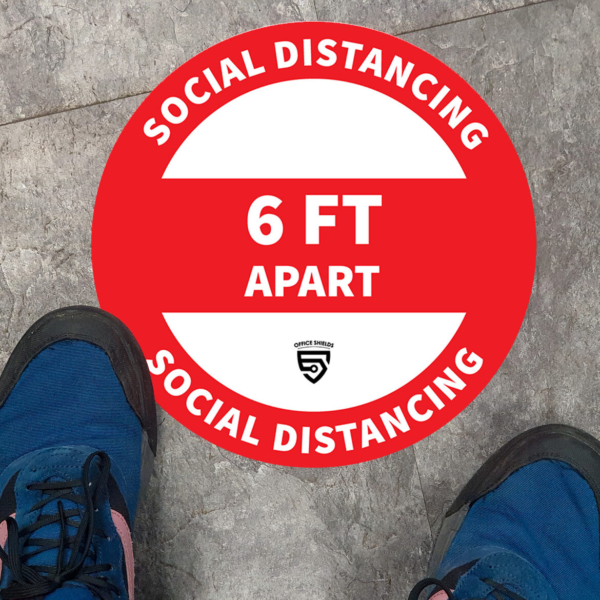 persons feet standing by a social distancing ground sign