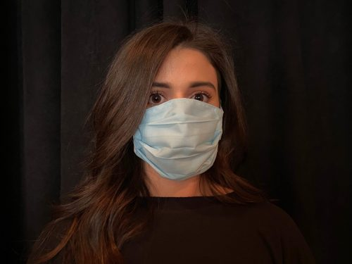 woman with dark hair against black background wearing a light blue cloth face mask
