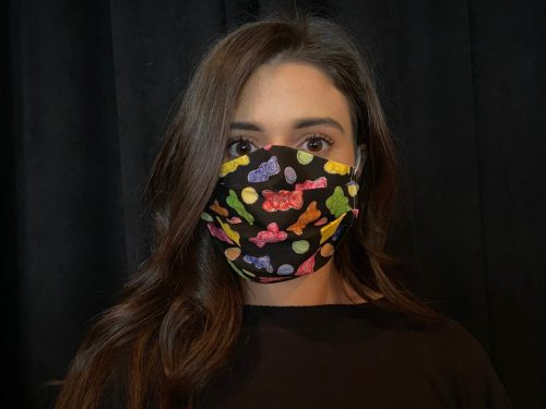 woman with dark hair against black background wearing a cloth face mask with a multicolor gummy bear print